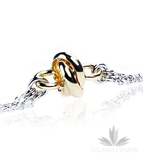 Bransoletka wykonana ze srebra próby 925, rodowana. Wyrób wykonany z trzech łańcuszków ozdobionych dodatkowo supełkiem o kolorze złotym, o średnicy około 1 cm. Bransoletka regulowana od 18 cm do około 22 cm. Dodatkowo do kompletu wystepuje także naszyjnik oraz kolczyki dostępne na stronach Galerii.   W całości komplet prezentuje się subtelnie i z klasą, dzięki złotym elementom można go łączyć ze złotą biżuterią.