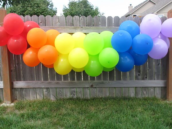 cluster of same color balloons tied together on string to make rainbow