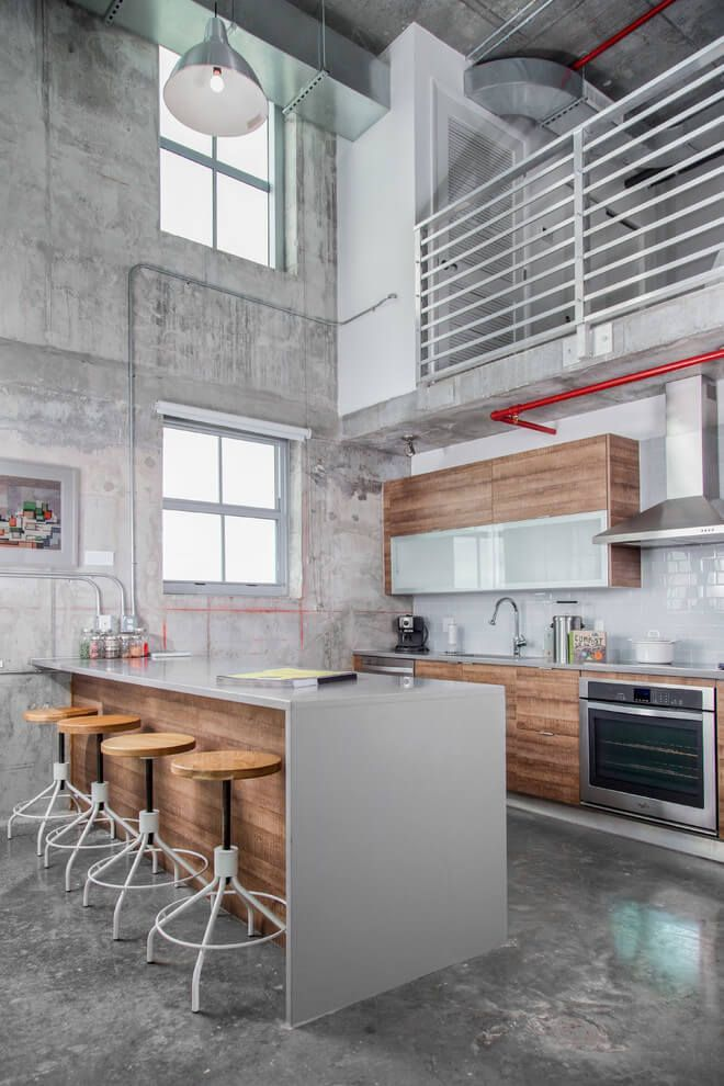 This inspiring industrial loft apartment is located in Miami Shores, Florida. The industrial mix of concrete and wood make for a great modern kitchen. It's very open too!