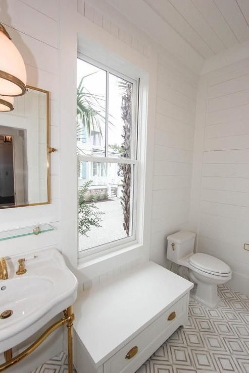 Gorgeous bathroom lined with white and gold diamond patterned floor tiles boasts a brass washstand with a white porcelain sink fitted with a brass faucet placed under a vintage glass shelf and a rectangular brass pivot mirror illuminated by a glass and brass pendant as a white bathroom window seat completed with polished brass cup pulls sits under a window surrounded by shiplap walls continuing up the ceiling.