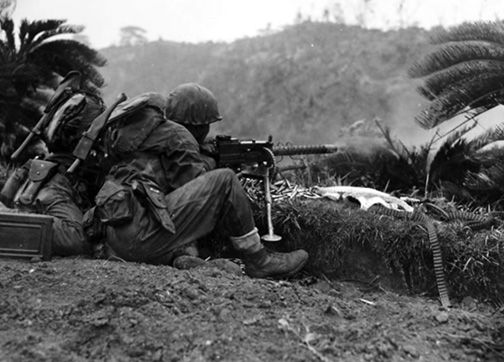 1945-Marines in combat on southern Okinawa. A .30-caliber light machine gun lays down fire support for an infantry attack. These automatic weapons were crucial elements in the rifle company's operations.