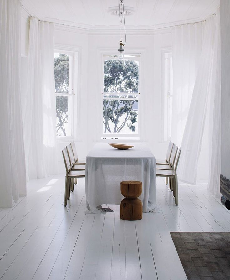 an amazing dining room in white and a gorgeous garden view Est Magazine