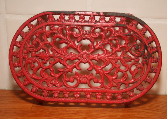 Red enameled cast-iron dish below.  Pot rack. Plate enamels old. Vintage dish below.    Industrial décor.