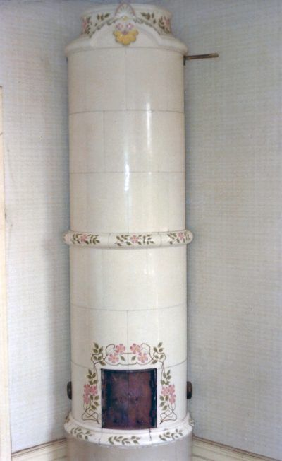 White 18th century style tile stove with coloured decorations. Karlskrona Kakelfabrik (tiled stove manufacturer), ca 1895. Height 267 cm.
