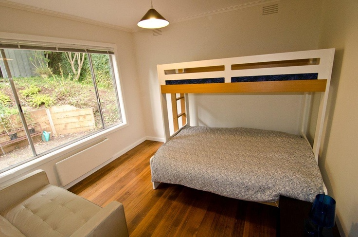 The third bedroom - double bed, single bunk with a 2 seater leather lounge and garden views.