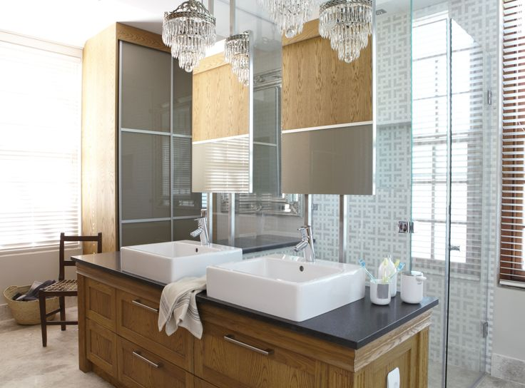 The shower glass makes up the back of the vanity and the mirrors are suspended and fixed in the bulk head.