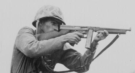 thompson submachine gun ww2 | American soldier fires Thompson submachine gun (WW2).