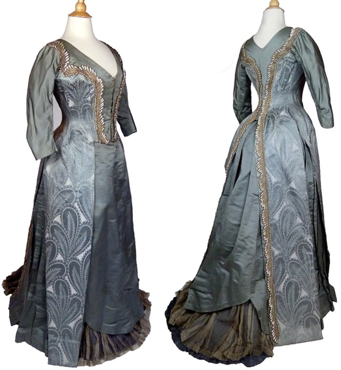 Reception gown, Emile Pasquier, ca. 1885. Two-piece ensemble with tailed bodice of triple plume pattern brocade and trained satin skirt. Bodice trimmed with large teardrop-shaped faux pearls, accented with looped silver tinsel & crystal beads. Skirt hem deeply scalloped at center front above pleated silk chiffon over cadet blue silk underskirt. Antique-Textile.com