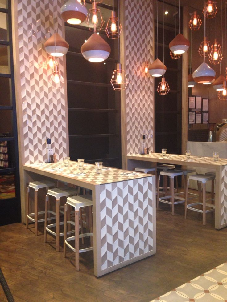 Cotta restaurant. Tessellated tiling on the tables continuing up the wall, helps tie in all of the colours and different materials and themes going on in the restaurant. Neutral tones and colours help tie together this beautiful look.