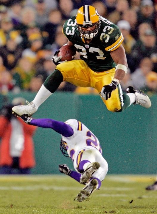 Nov. 14, 2004 - FB William Henderson (33) leaps over Vikings CB Antoine Winfield in the second quarter at Lambeau Field. The Packers won, 34-31.