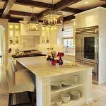 kitchens - white glass-front shaker kitchen cabinets white kitchen island calcutta gold countertops gray square lanterns pot filler rustic exposed wood beams farmhouse sink