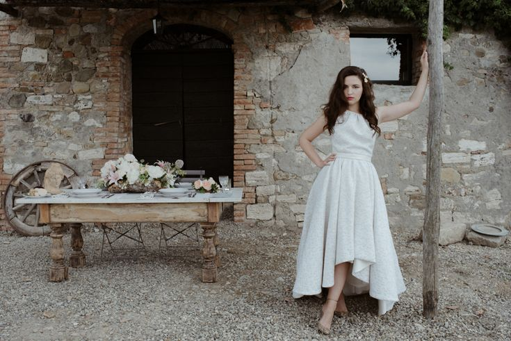 "Untraditional 'Clò' high-low wedding dress is so different and unique, it has a higher hem at the front and a dip hem to the back. Fun and flirty, legs staged their glorious; by MARIANNA LANZILLI Handmade gold bronze BROOCHE ""ACANTO"" with Crystal swaroski by CHIARA BCN ornates Anja's wawy hair ."
