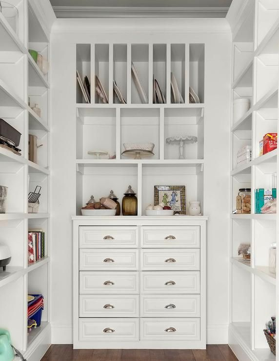Beautifully organized kitchen pantry features white built in shelves flanking a wall fitted with vertical tray shelves fixed above display shelves placed over white built in cutlery and linen drawers adorned with polished nickel cup pulls.