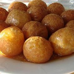 loukoumades - greek fried donut balls with honey syrup.  Delicious served warm with chopped walnuts on top!  For very light donuts, add water until dough is almost pourable, pull it up in spoonfuls and use your finger to drop it in hot oil.  Not as pretty or round, but oh so nice and soft with a crunchy crust.