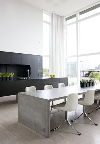 Concrete table and black kitchen.