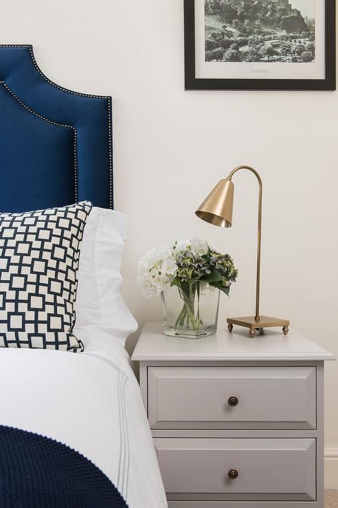 Sophisticated bedroom features a blue velvet headboard with silver nailhead trim on bed dressed in white and blue stitched hotel bedding and a navy cat's cradle pillow next to a gray nightstand adorned with brass knobs topped with a brass task lamp.
