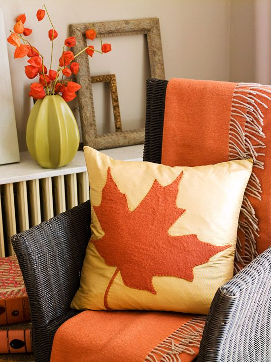 Dress up your furniture with cozy items in seasonal colors. Here, a wicker chair is draped with a warm orange throw, and a maple leaf pillow sits comfortably on top. Perk up a plain pillow by enlarging a leaf using a copier to make a pattern. Cut the pattern out of wool felt and attach it to the pillow cover using iron-on fusible backing. Blanket-stitch around the edges.