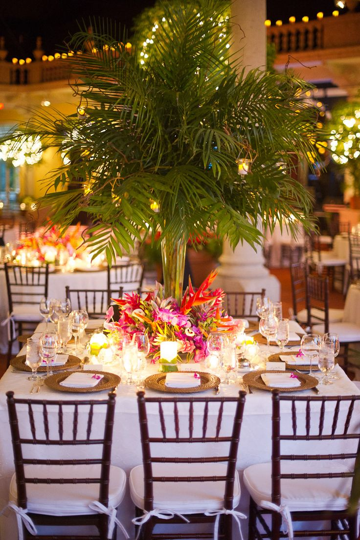 "Tropical Wedding Centerpiece, with curly willow holding votives. Also gold mercury votives on table. Pilsner vase..28"". Possibly gold tablecloth."