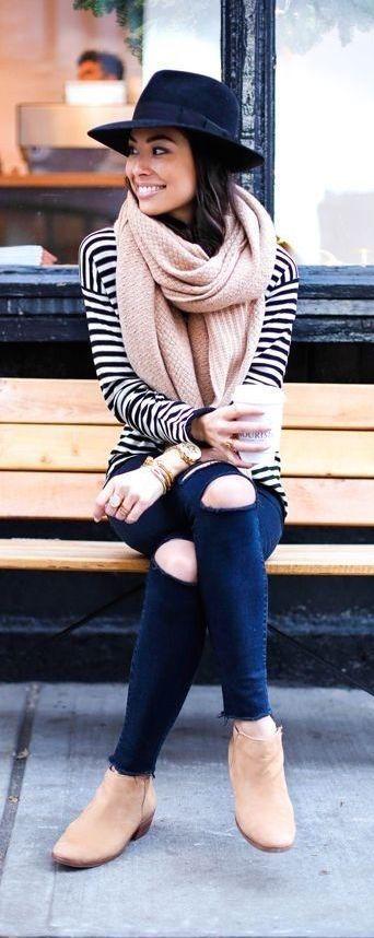 Sombrero negro, sweater a rayas, bufanda rosa viejo, jeans con roturas en rodillas, botinetas.