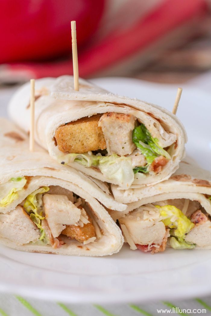 Chicken Caesar Wraps - simple, delicious and the perfect recipe for lunch or a picnic. Yummy romaine, chicken, bacon, croutons, and caesar dressing all wrapped in a flour tortilla!