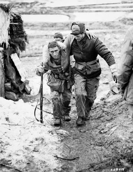 Private Morris J Piche is helped to an aid station behind the front lines in the Kapyong Valley by Lance Corporal W J Chrysler, both of the PPCLI. Korean War, 1950-1953.