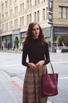 Pair a timeless black long-sleeve with an equally timeless striped midi skirt.