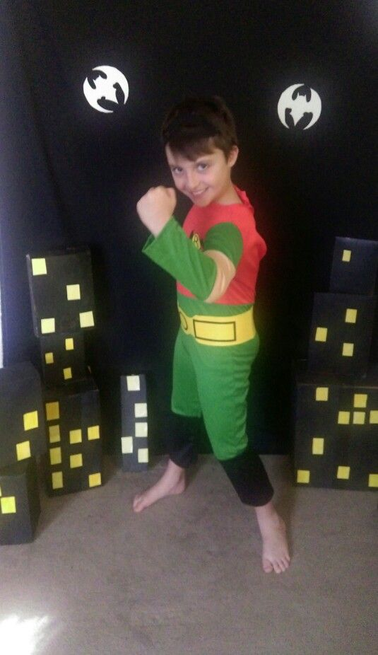 Super hero birthday party boy. Dressed as robin.  Back drop I hung black material stuck on some bats. Painted various boxes to make sky line... Perfect photo opportunities