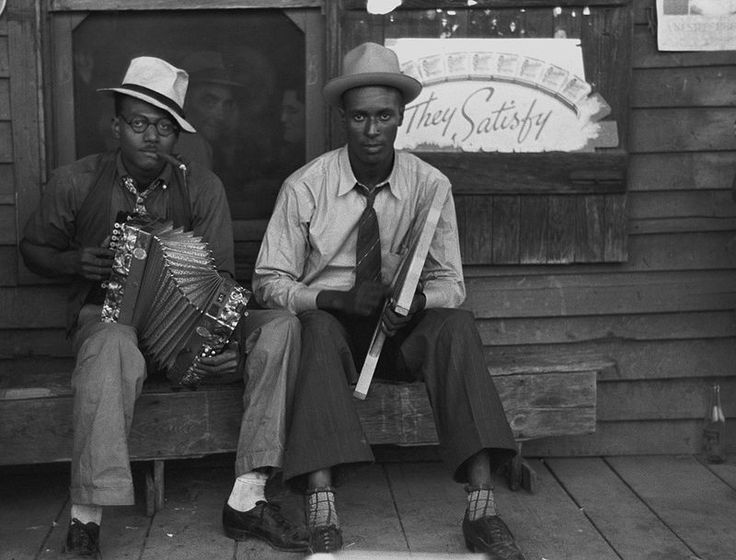 """Early Creole musicians playing an accordion and a washboard in front of a store, near Opelousas, Louisiana (1938). Zydeco music originated from Creole music — today's rubboard or frottoir (""""rubbing the washboard"""") is a stylized version of the early washboard."""