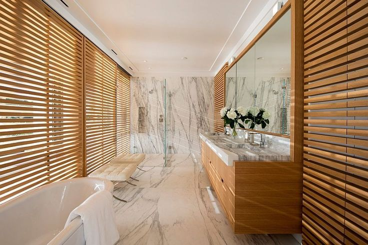 Narrow Bathroom with Wooden Sun Shade containing: Wooden Floating Vanity with Granite Vanity Top also Large Mirror plus Freestanding Tub together with Tufted Bench with Large Granite Flooring And Wall