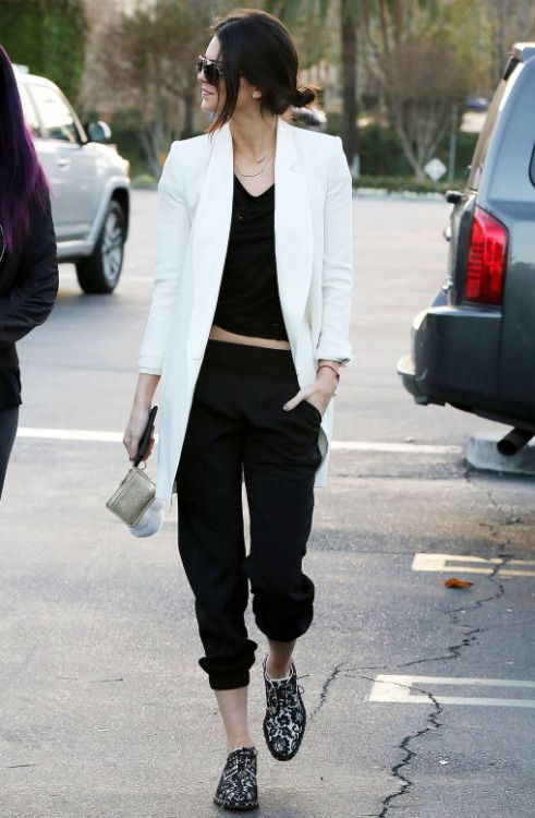 Model off-duty street style fashion: Kendall Jenner in white blazr + black top and pants minimal chic style.