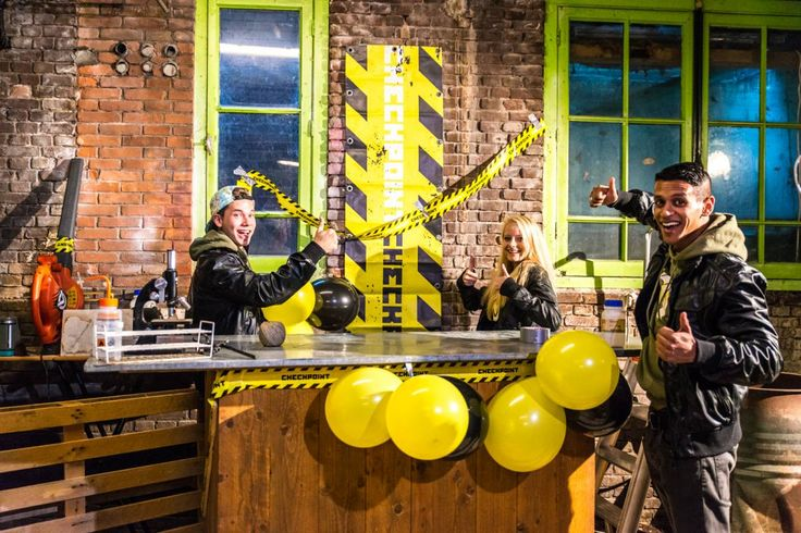 Een desk maken, en verder gele ballonnen, geel-zwart lint, etc gebruiken om het aan te kleden in checkpoint style