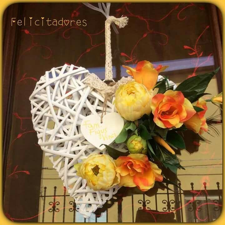 Cuore in vimini decorato con fiori finti, sui toni dell'arancione...