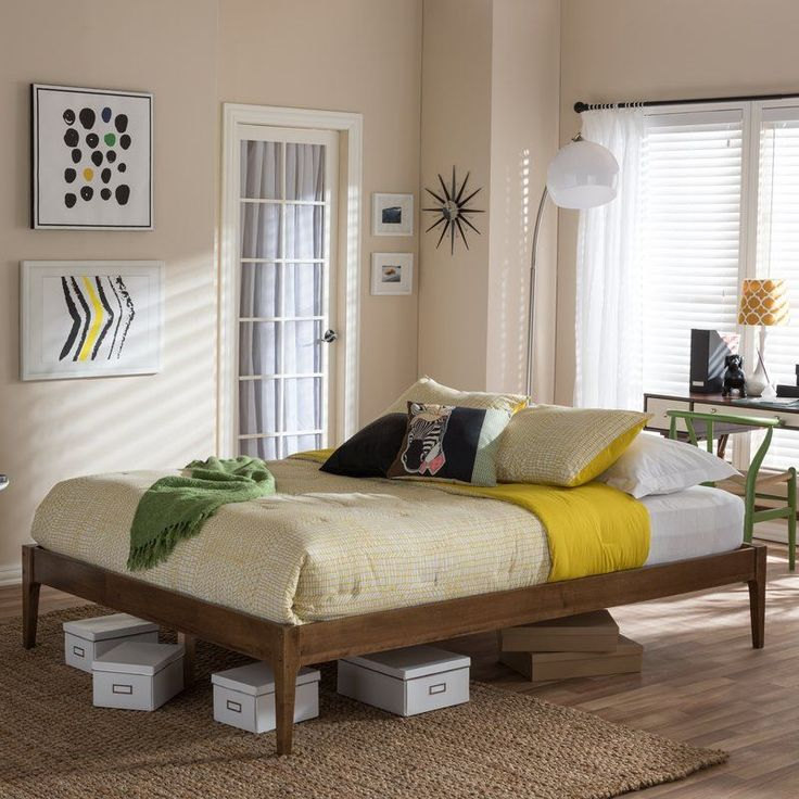 Blend modern sophistication and transitional appeal in your master suite or guest bed room with this understated and chic platform bed, featuring gently angled legs and a sturdy rubberwood design. Let it anchor your loft-worthy master suite with comfy Egyptian-quality cotton sheets and a muted yellow comforter, then top it off with popping geometric duvet covers for an added dash of fashionable feel. To complete the look, set down a neutral-toned jute rug for breezy appeal, then line the…