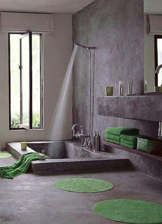 I liked the use of negative space in this room.  The positive space is the floor and the part that has been cut out and left empty has been turned into a bathtub.  The green accent rugs and matching towels also bring life and color. The circular rugs also add contrast to an otherwise strictly rectangular room.
