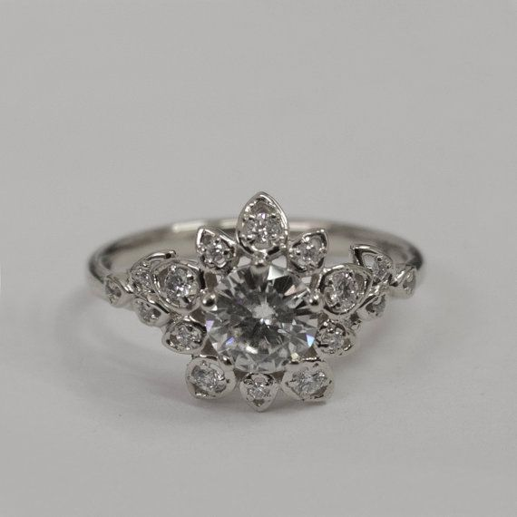 A handmade 14k white gold ring showing a delicate flower set with a beautiful clear diamond at the center and smaller clear diamonds in the