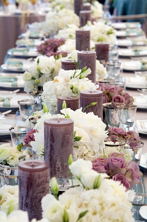 Pillar candles in varying heights are staggered throughout the center of this long banquet table, creating a visually dynamic runner.