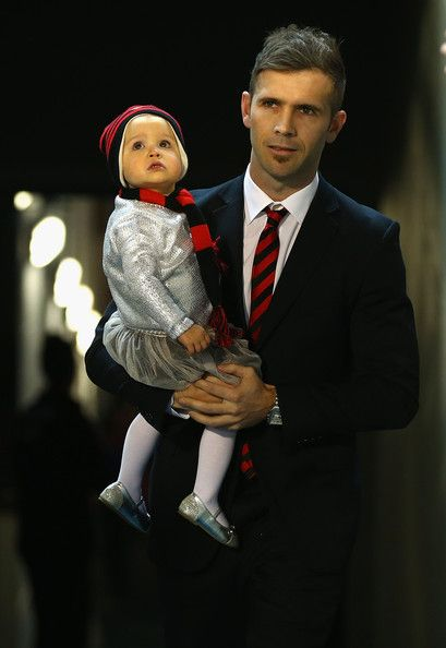 "AFL Rd 23 - Essendon v Collingwood Mark ""Spike"" McVeigh with his daughter Ariana walking out for the last time onto the G after announcing his retirement after 232 games."