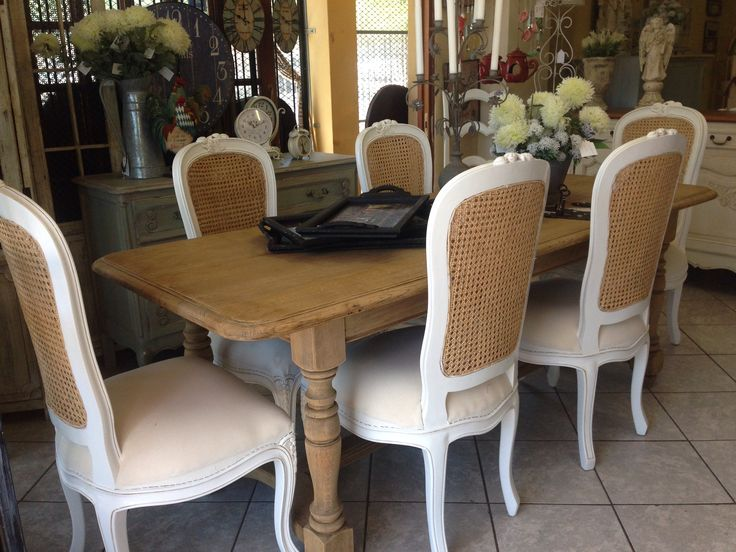 Gorgeous vintage provencal dining table of bleached oak. The chairs are signature Louis XV style dining chairs with rattan back