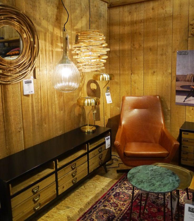 Fauteuil met cognackleur in woonkamer met goudkleurige lampen en vintage accenten. Zen Lifestyle is gevestigd in Wijchen bij Nijmegen en heeft showroom van 10.000 m². Natuurlijk vind je in onze winkel onze eigen producten, zoals ons aanbod vintage en retro banken, onze topsellers, zoals het vintage tv-dressoir Stan. Maar ook hebben wij de mooie collectie van Zuiver en Duchtbone en vind je er nog veel meer topmerken, zoals Be Pure, JouwMeubel, UrbanSofa, Fatboy, Makkii, Woood etc.
