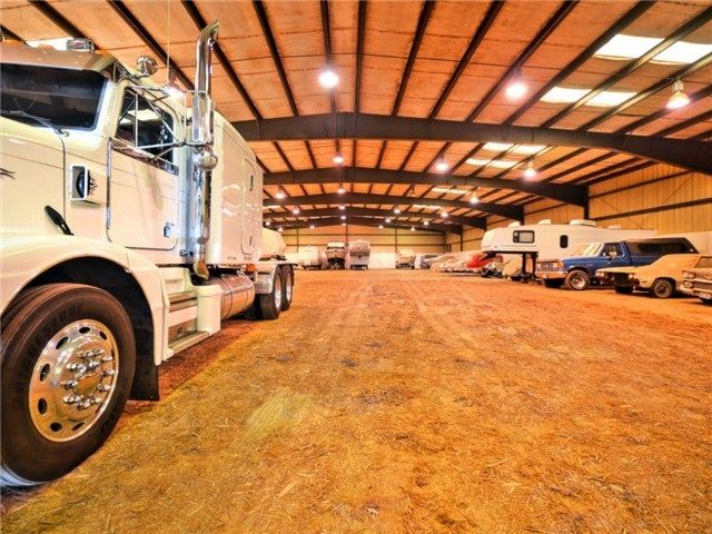 The semi truck gives you a sense of scale of how large this arena is. Currently used for storage and a Mechanic's Dream shop but is still an operational equestrian arena. Bring your horses or your own car collection.