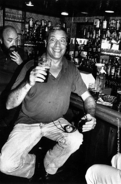 1984: Film star Oliver Reed pulls a face for the photographer  while enjoying a pint of beer in a well stocked bar.