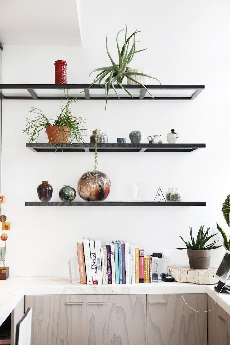 Love these modern and minimalist black open shelves in the kitchen, topped with potted indoor plants and collection of cookbooks!