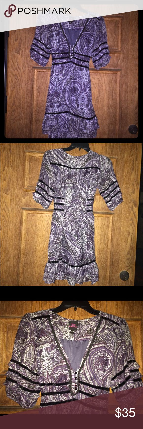 """BEBE Purple Paisley Mini Dress Tunic Size Small Bebe Mini Dress Tunic. Soft polyester fully lined with form flattering tie in back. About 30"""" long - it's just barely a mini dress on me at 5'3"""" - would be a tunic on anyone taller. Lace trim around neckline and velvet stripes around skirt hem, waist and sleeves. Ruffles on sleeves and hem. 4 buttons at bust. Light pilling on exterior but due to pattern can't see it. Cozy and unique. bebe Dresses Mini"""