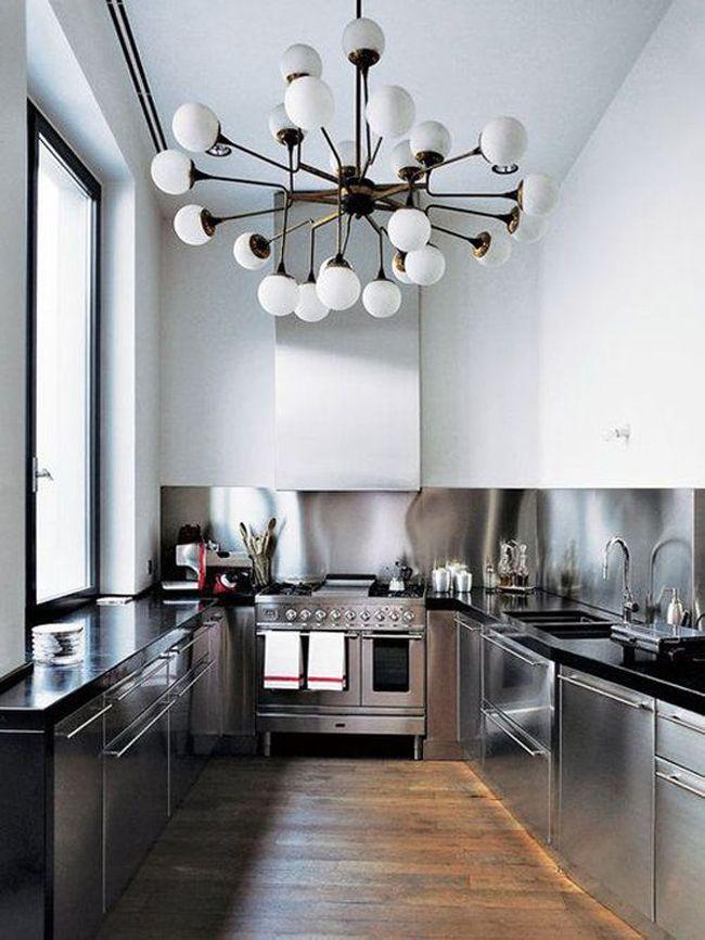 Cocina de estilo industrial en esta reforma de piso con techos altos e impresionante araña de esferas de cristal.
