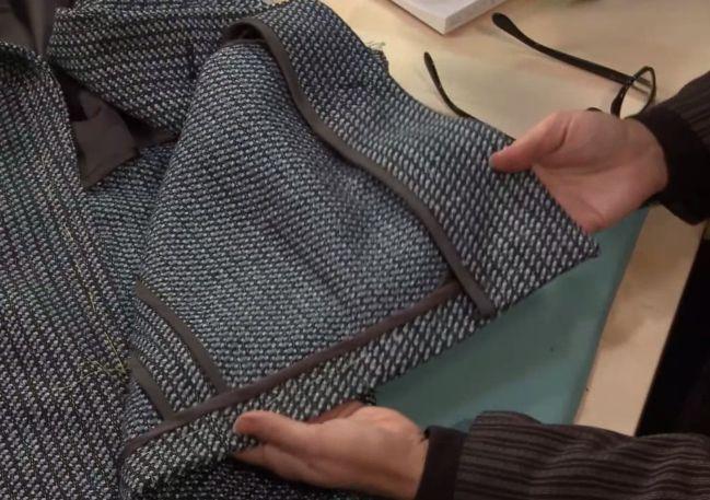 Man Displays the Inside of a Coat, Showing Seams Hong Kong seam finish
