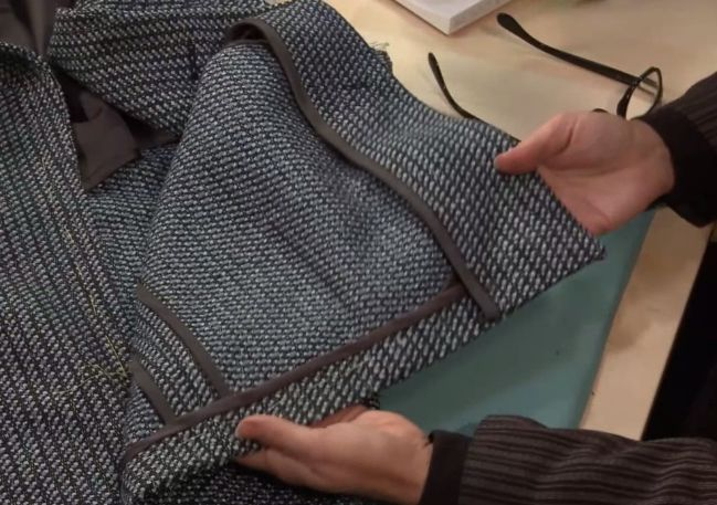 Man Displays the Inside of a Coat, Showing Seams Hong Kong seam finish