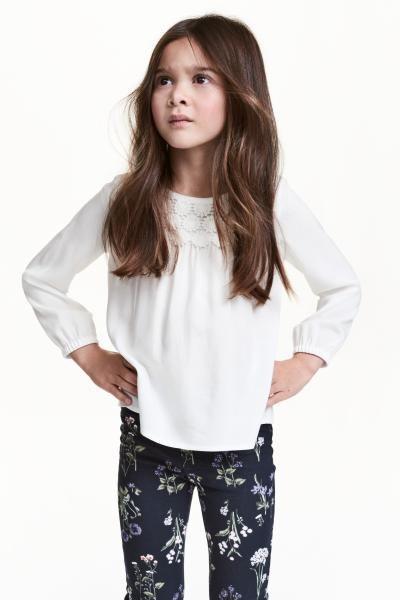 Blouse met kant: Een blouse van zachte, geweven kwaliteit met een ruime pasvorm. De blouse heeft kant boven aan de voorkant, een splitje met een knoop in de nek en lange mouwen met smal elastiek onderaan.