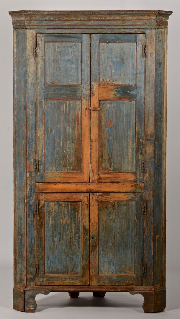 "1820 SC or NC Piedmont yellow pine corner cupboard in the original painted blue surface, one piece construction. Cove cornice with carved rope top edge, upper two doors with two inset panels each over lower paneled doors, ogee moldings to returns and base, bracket feet with returns. Top section interior with three shelves having scratch beaded edges, center shelf having a plate ledge. Lower interior with one shelf. Interior retains much of the original brown paint. 88""H x 47 1/2""W. Cir"