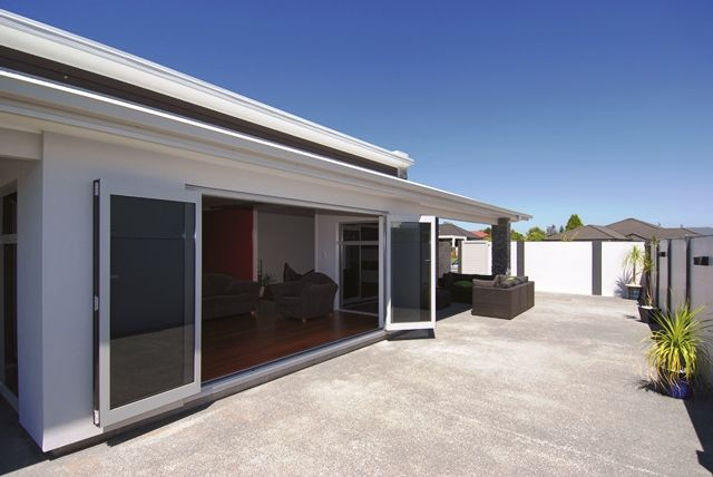 Bi-folding doors in the living room and lounge provide access to the home's outdoor living space.