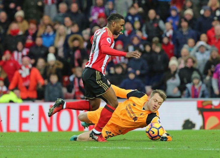 Liverpool brankár Simon Mignolet robí zákrok proti Jermain Defoe